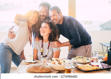 Group of friends have fun together during a lunch outdoor in the terrace at home and taking a modern selfie with smart phone to share on social media accounts for internet life - web addicted happy
