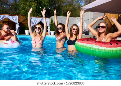 Group of friends have pool party dancing with inflatable floaty, watermelon swim ring toys. Attractive hot pretty women in bikini and sunglasses have fun relaxing and chilling on sunny summer day.