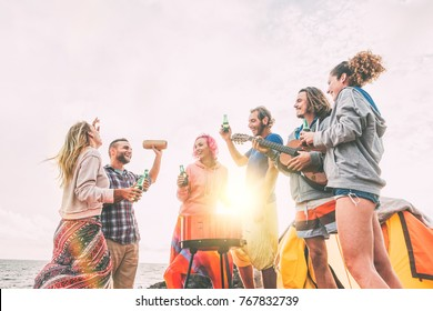 Group of friends having barbecue drinking beers while camping on the beach - Happy people enjoying camp bbq playing guitar, singing and listening music at sunset -  Friendship, adventure concept