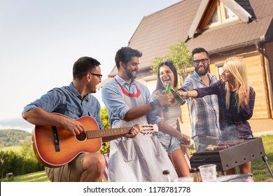 Group of friends having a barbecue party outdoors, drinking beer, grilling meat, playing the guitar, singing and having fun