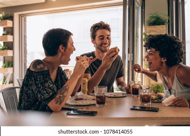 Group of friends having burger at restaurant. Cheerful young people eating burger and enjoying at a fast food restaurant.
