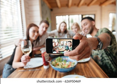 Group of friends having dinner and taking selfie with smartphone at the table