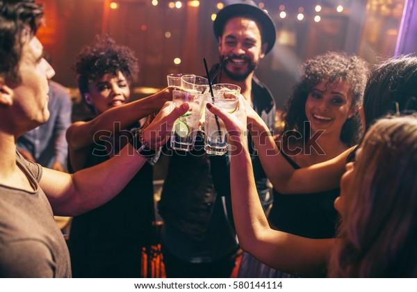 Группа друзей, которые пьют на вечеринке в ночном клубе. Молодые люди наслаждаются в баре тосты коктейлей.
