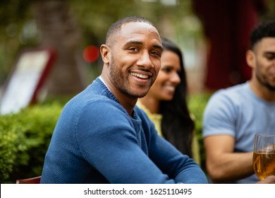 A group of friends having drinks outdoors at a bar. The main focus is a man smiling and looking at the camera.