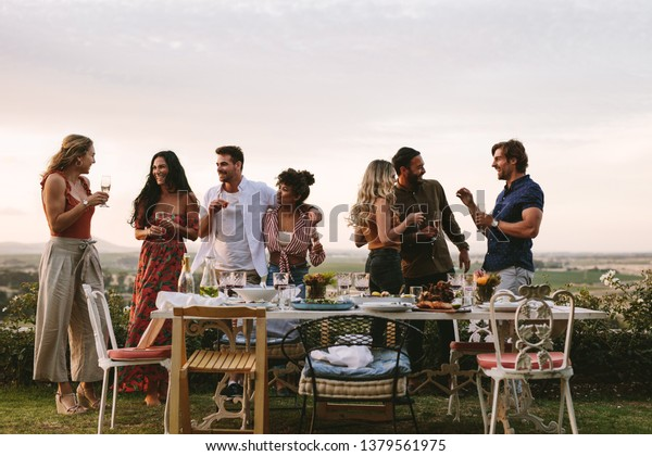 Group of friends having drinks at party in garden. Millennials enjoying dinner party outdoors.