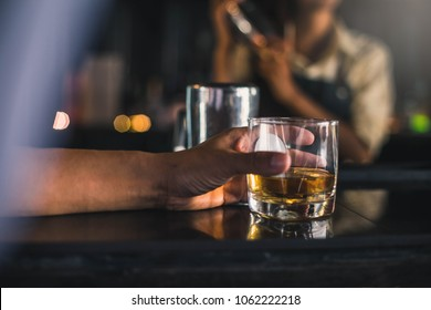 Group of friends having drinks whiskey at the night club after work . Young men drink whiskey and enjoying at a bar toasting cocktails.