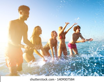 Group of friends having fun at the beach with water sea