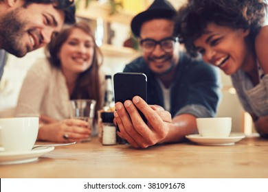 Group of friends having fun at the cafe and looking at smart phone. Man showing something to his friends sitting by, focus on mobile phone.