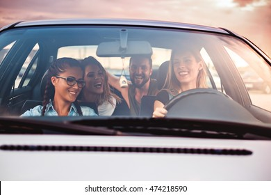 Group of friends having fun in the car. Sunset