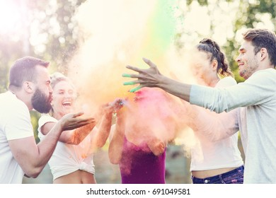 Group of friends having fun at color festival