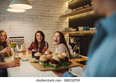 A group of friends having fun at dinner in the kitchen.