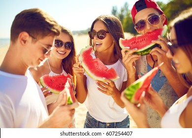 Group of friends having fun eating watermelon. on the beach. Excellent sunny weather. Beautiful figures. Super mood. Summer concept