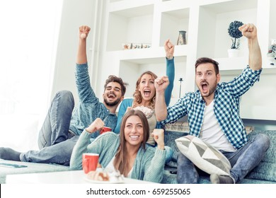 Group of friends having fun at home,watching game and enjoying together.