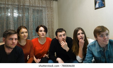 Group of friends having fun at home,watching game and enjoying together. Friends are watching football match at home