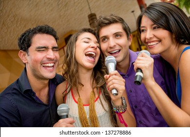 Group of friends having fun karaoke singing at the bar