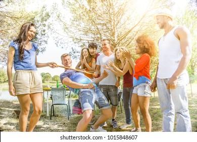 group of friends having fun, limbo dancing outdoors