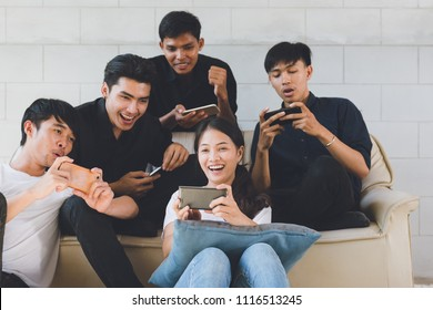 Group of friends having fun at living room and looking at smart phone, Asian teen watching football game in Mobilephone.