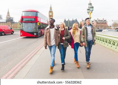 Group of friends having fun in London. Mixed race people laughing and enjoying their time in the city. Big ben and double decker red bus on background.