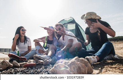 Group of friends having fun making BBQ on bonfire and relaxing by a lake.