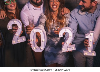 Group of friends having fun at New Year's party, holding illuminative numbers 2021 representing the upcoming New Year at midnight countdown
