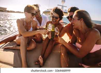 Group of friends having fun on a yacht, drinking wine and laughing. Party on the private boat.