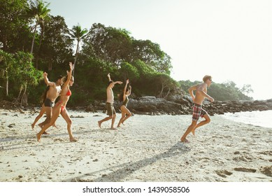 Group of friends having fun on the beach on a lonely island. six people celebrate their vacation in Thailand enjoying the nature. Lifestyle concepts