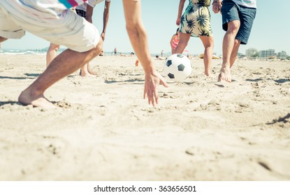 Group of friends having fun on the beach playing soccer. happy people and beach games concept