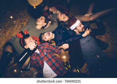 Group of friends having fun on a floor, celebrating New Year