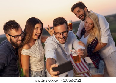 Group of friends having fun at an outdoor summertime party, dancing, drinking beer and taking selfies