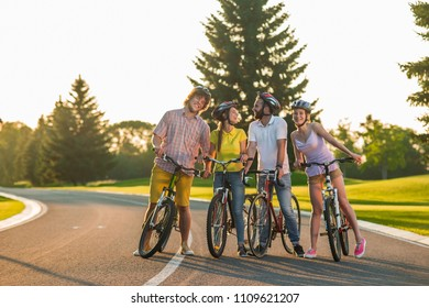 Group of friends having fun outdoors. Four happy students with bikes resting on the road. Enjoy your cycling more.