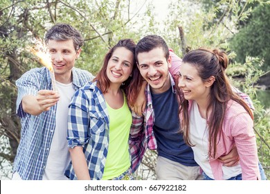 group of friends having fun outdoors on a summer sunset, they hold spark sticks in their hands