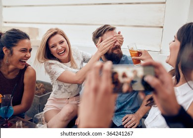 Group of friends having fun at a party with man taking a photo on a smart phone. Young people enjoying a party together.