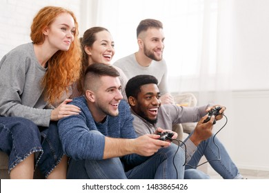 Group of friends having fun, playing video games at home, free space