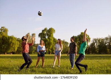 Group of friends having fun playing with a ball on a grass picnic in a summer park.