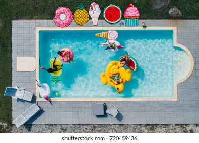Group of friends having fun in the pool with different air beds