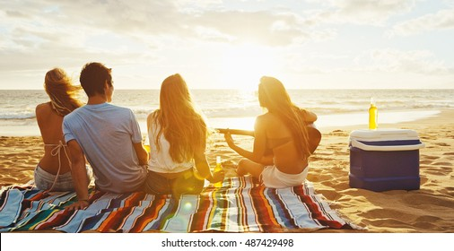Group of friends having fun relaxing on the beach at sunset