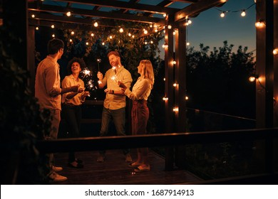 Group of friends having fun with sparklers at the terrace party