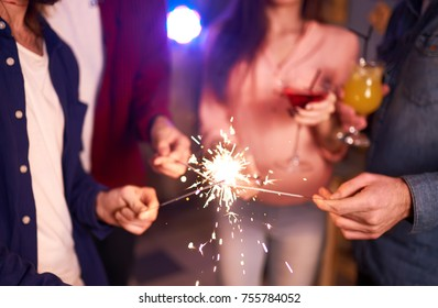 Group of friends having fun with sparklers.  young people laugh. celebrating New Year together. Group of beautiful young people in Santa hats. Blur Background