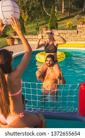 Group of friends having fun at a summertime poolside party, playing volleyball in the swimming pool