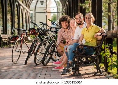 Group of friends having fun together outdoors. Friendly students resting with bicycles in park. Active lifestyle concept.