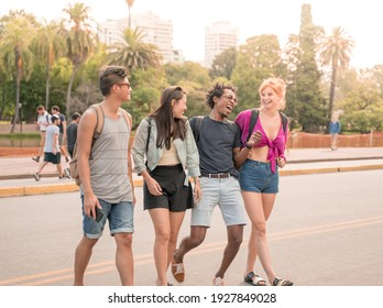 A group of friends having fun together in the city on a sunny warm summer day.