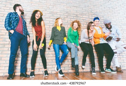Group of friends having fun together. Mixed race group of teenagers posing against the brick wall
