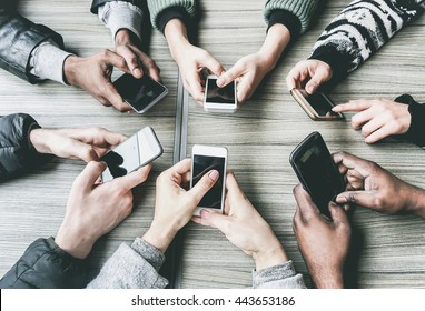 Group of friends having fun together with smartphones - Closeup of hands social networking with mobile phones - Technology and phone addiction concept - Main focus on bottom hands - Vintage filter