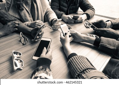 Group of friends having fun together with smartphones - Closeup of hands social networking with mobile phones - Black and white editing - Technology addiction concept - Main focus on center hands