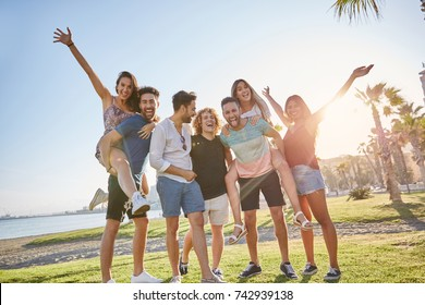 Group of friends having fun together outside in sunlight