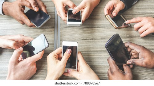 Group of friends having fun together with smartphones - Closeup of hands social networking with mobile cellphones - Wifi connected people creative office - Technology and phone addiction concept