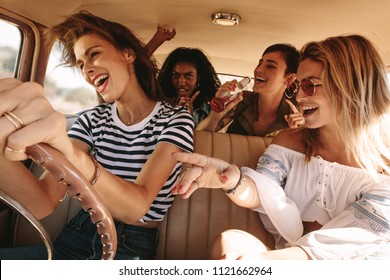 Group of friends having fun, traveling in car. Happy smiling young women on a road trip during summer vacation.
