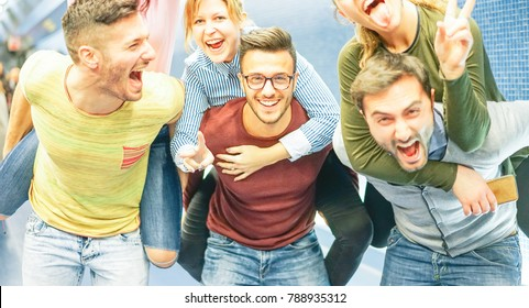 Group of friends having fun in a underground station - Men piggybacking their girlfriends - Young people making party - Concept of friendship, lifestyle and youth