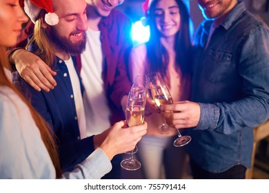 Group of friends having fun. young people laugh. celebrating New Year together. Group of beautiful young people in Santa hats. Blur Background