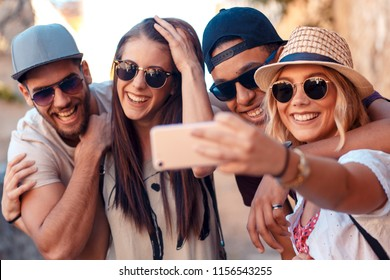 Group of friends having good time at the city street making selfie.